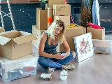 Femme consultant son smartphone pendant un déménagement