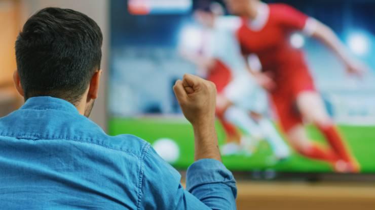 Un homme regarde du football à la télévision