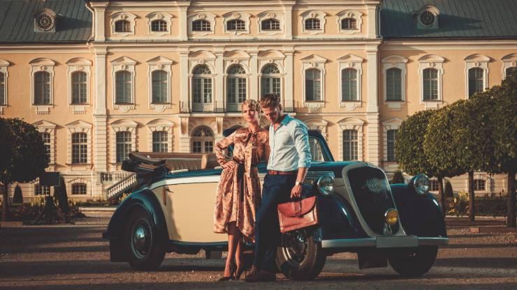 Couple aisé devant une demeure