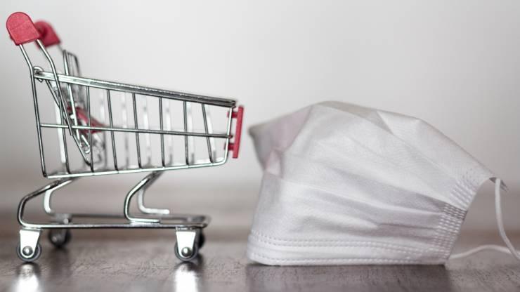Masque chirurgicale à côté d'un chariot de supermarché