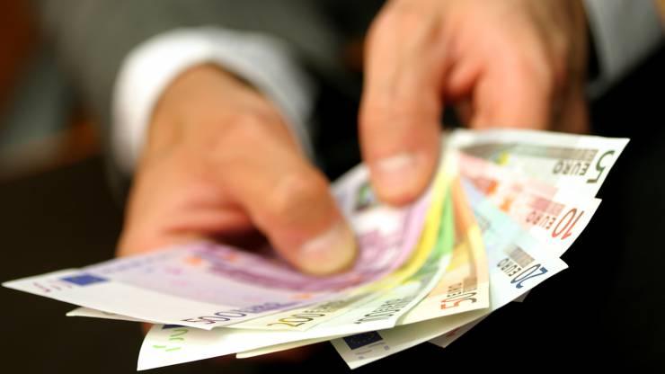 un homme tenant des billets en euros