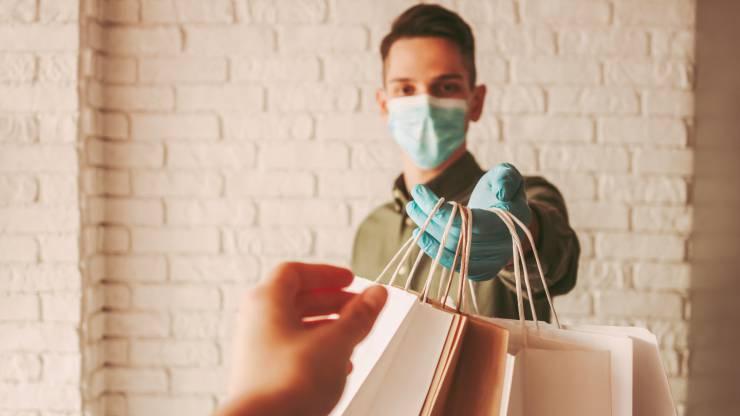 Un homme masqué délivre des sacs de courses à une femme