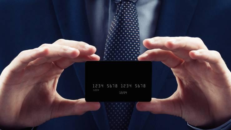 Un homme en costume présente une carte bancaire noire