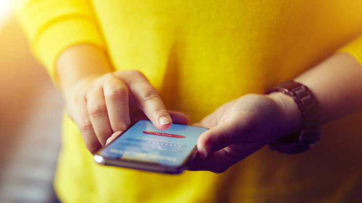 Une femme se connecte à l'application mobile de sa banque