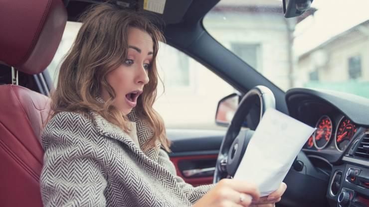 Femme lisant une facture au volant