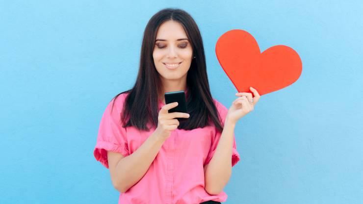 Une femme consulte un smarphone, un coeur dans la main