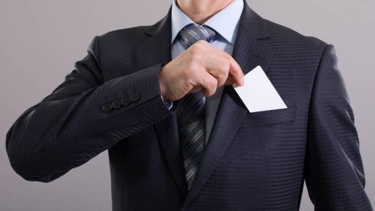 Un homme en costume range sa carte bancaire dans sa poche