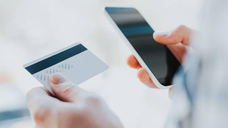 Un jeune homme consulte son mobile et tient une carte bancaire