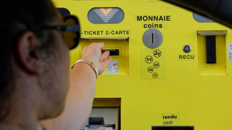 Une femme paye par carte à un péage