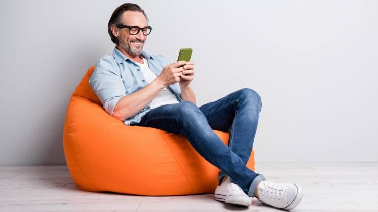 Un homme souriant consulte son smartphone assis sur un pouf