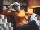 Femme masquée et rouleaux de papier toilette