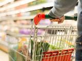 Une homme pousse un chariot dans un supermarché