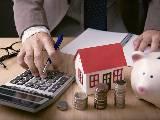homme utilisant une calculatrice pour optimiser son prêt immobilier