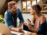 Couple discutant devant un ordinateur, carte bancaire à la main