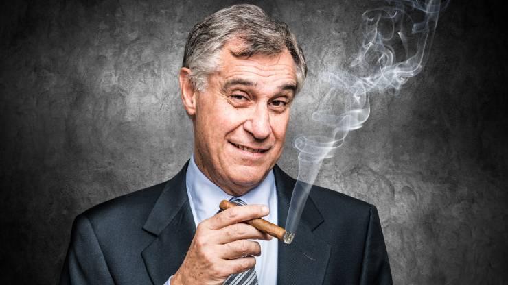 Un homme d'affaire souriant fume un cigare