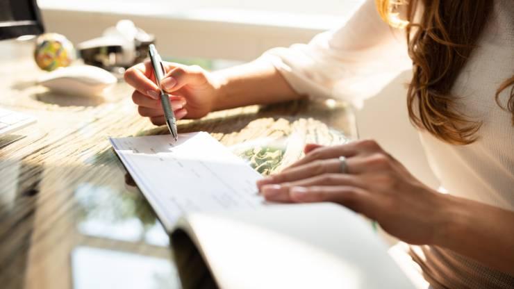 Une femme signe un chèque